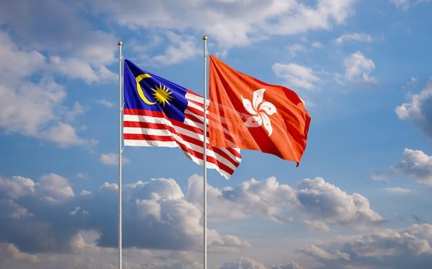 Die flaggen von malaysia und hongkong fliegen zusammen im wind gegen den wolkigen blauen himmel.