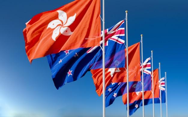 Die flaggen von neuseeland und hongkong fliegen zusammen im wind vor dem blauen hintergrund