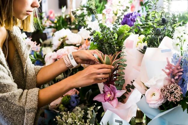 Die floristin korrigiert die blumensträuße auf der theke. blumenmarkt
