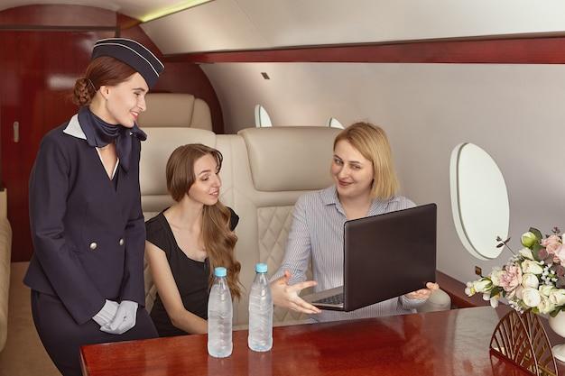 Die flugbegleiterin bedient passagiere im business-jet. eine stewardess kommuniziert mit jungen frauen erster klasse.