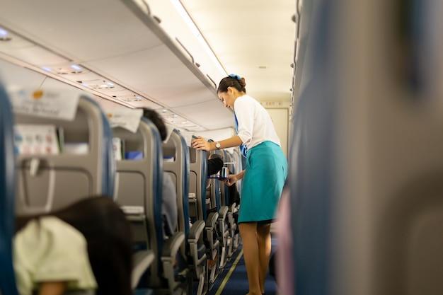Die flugbegleiterin von bangkok airways serviert den passagieren getränke