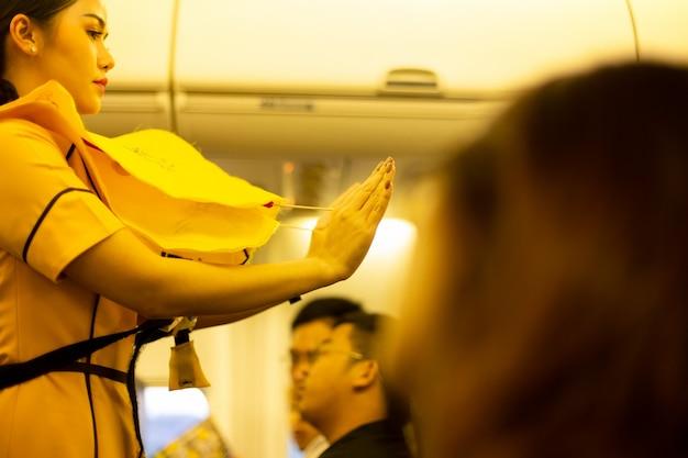 Die flugbegleiterin weist die passagiere in die benutzung der schwimmweste an bord ein