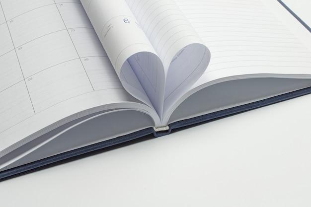 Die form des herzensliebeskonzepts aus zwei tagebuchseiten, die zu einer herzform werden. bücherwurm oder buchliebhaber, sauberer und unscharfer hintergrund.