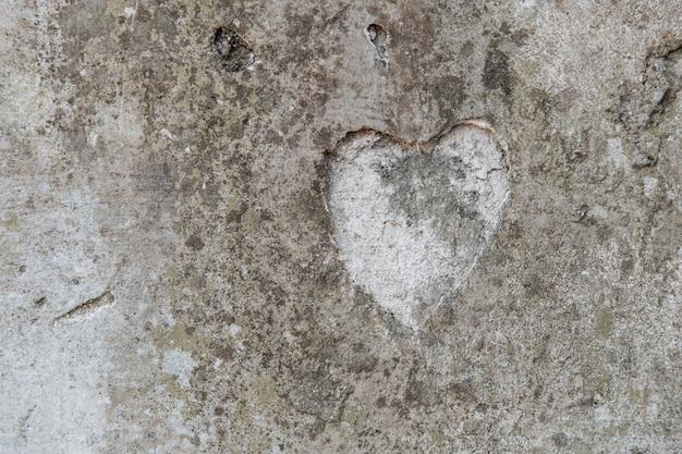 Die form eines herzens auf einer alten betonmauer
