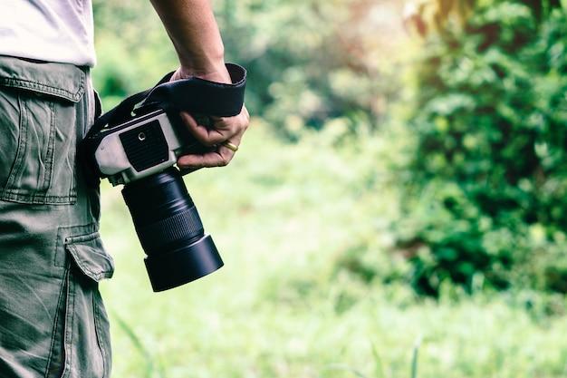 Die fotografie, die dslr kamera in wildem hält.