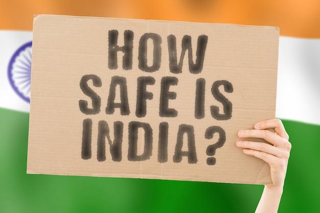 Die frage wie sicher ist indien auf einem banner in der hand eines mannes dangerous security attack criminal