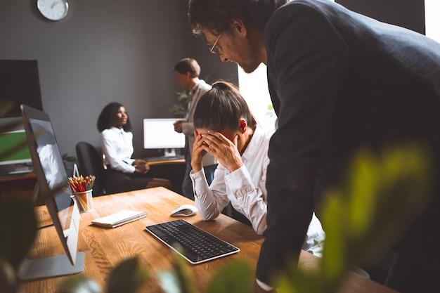 Die frau bedauert den fehler, den sie im projekt vor dem senior mentor gemacht hat. die mitarbeiter arbeiten hart im team, um das projekt umzusetzen. teamwork-konzept.