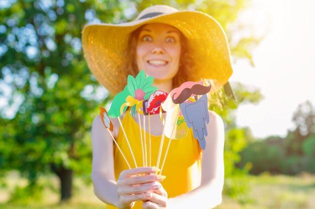 Die frau der glücklichen schönheitskomikfrau trägt gelbes sommerlichtkleid und sommerhut, die sonnigen tag im freien im grünen park mit bunten party requisiten genießen. aktives lustiges outdoor-freizeit-lifestyle-konzept.