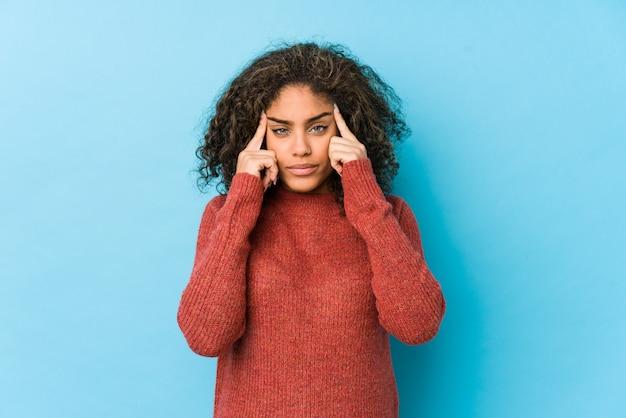 Die frau des gelockten haares des jungen afroamerikaners konzentrierte sich auf eine aufgabe und hielt die zeigefinger, die kopf zeigen.