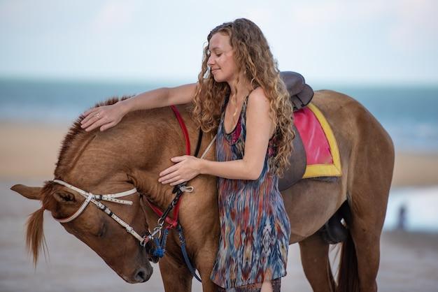 Die frau des gelockten haares, die das pferd am strand bereitsteht, reisen und entspannen sich konzept.