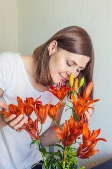 Die frau des hauses atmet den duft von orangenlilien ein, die in einer vase stehen