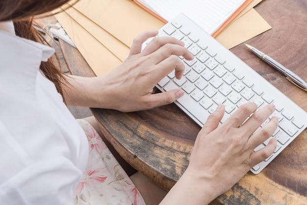 Die frau, die an hand auf computertastatur, schwachem licht, selektiver fokus schreibt, kann für e-commerce-, geschäfts-, technologie- und internet-konzept verwendet werden