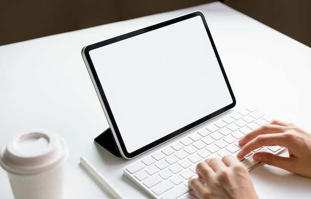 Die frau, die auf dem tisch tastaturlaptop- und -tablettenschirmleerzeichen schreibt, verspotten oben, um ihre produkte zu fördern. zukunftskonzept und trend-internet für einfachen zugang zu informationen.