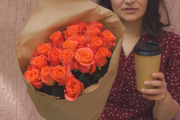 Die frau, die blumenstrauß von rosen und von papierschale von hält, nehmen getränk weg