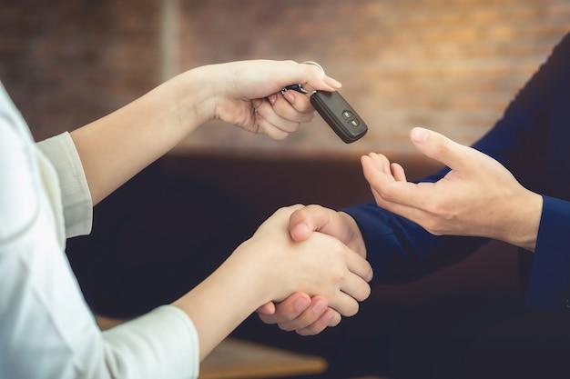 Die frau, die den schlüssel des autos hält, hat zugestimmt, dem kunden zu geben.