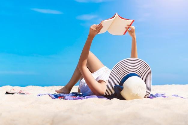 Die frau, die ein buch auf dem tropischen strand mit liest, entspannen sich im urlaub zeit.