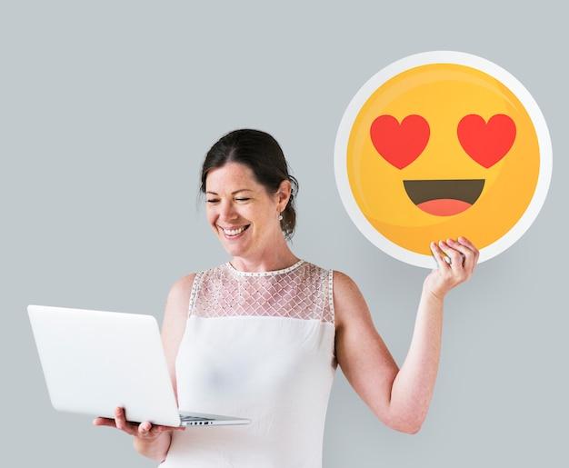 Die frau, die ein herz hält, mustert emoticon und einen laptop