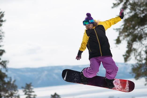 Die frau, die ein snowboard reitet, springt