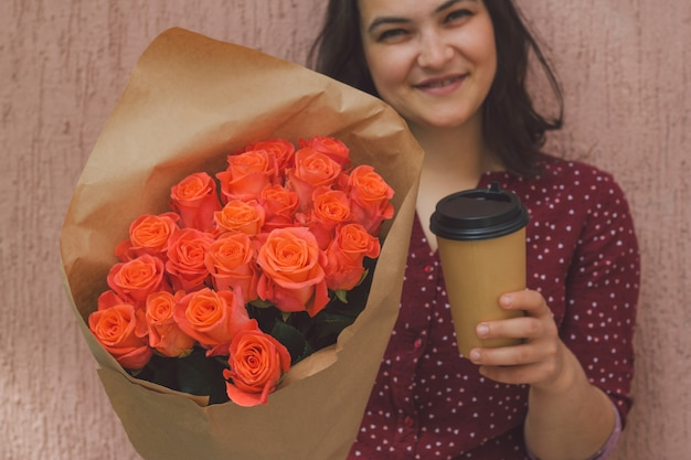 Die frau, die einen blumenstrauß von rosen und von papierschale von hält, nehmen getränk weg