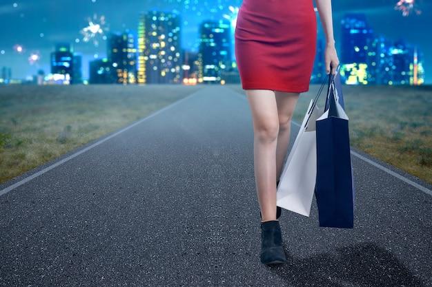 Die frau, die einkaufstaschen auf der stadtstraße trägt