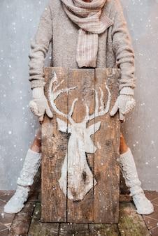 Die frau, die für winter mit weißen gestrickten modeeinzelteilen gekleidet wird, hält ein hölzernes plakat mit gemaltem weißem rotwildgrauhintergrund.