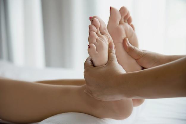 Die frau, die fußmassageservice vom nahem hohem der masseuse und fuß empfängt - entspannen sie sich im fußmassagetherapie-servicekonzept