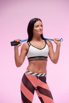 Die frau, die gegen rosa studio mit springseil trainiert