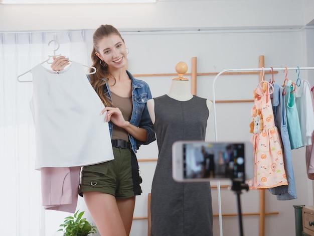 Die frau, die geschäft in ihrem haus tätigt, frauen bieten ihre kleidung für verkauf online an