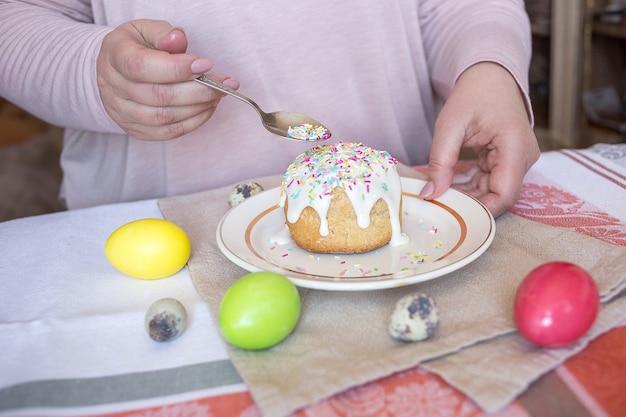 Die frau, die hinzufügt, besprüht auf die oberseite des ostern-kuchens. farbige eier auf einem tisch