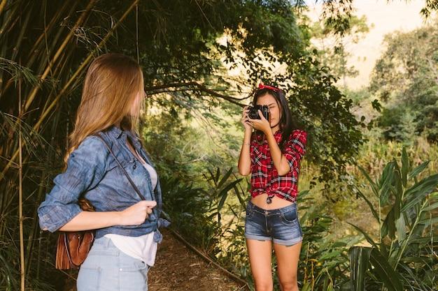 Die frau, die ihre freunde nimmt, fotografieren mit kamera im wald