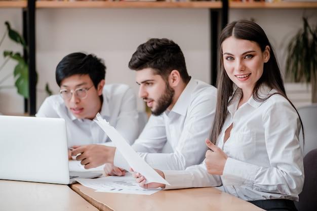 Die frau, die im büro arbeitet, zeigt sich daumen mit verschiedenen männlichen mitarbeitern