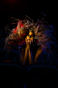 Die frau, die im theater die rolle eines geistes oder geistes spielt, sitzt zwischen den stuhlreihen