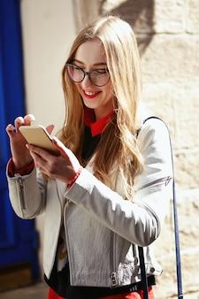 Die frau, die in der zufälligen art gekleidet wird, überprüft ihr telefon, das auf der straße steht