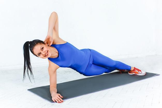 Die frau, die in einem fitnessstudio eines fitnesscenters trainiert