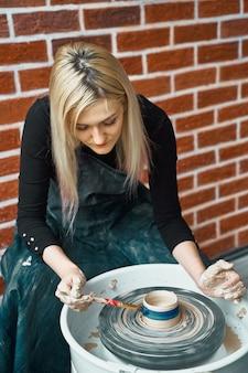 Die frau, die keramische tonwaren auf rad macht, malt blau. konzept für frau in freiberuflicher tätigkeit