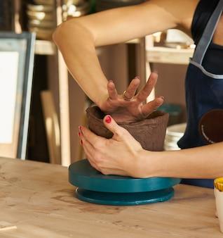 Die frau, die keramische tonwaren, handnahaufnahme macht, konzentrieren sich auf töpfer, palmen mit tonwaren