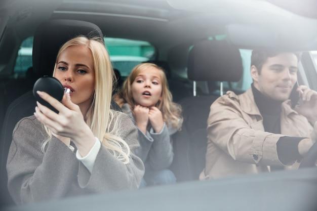 Die frau, die make-up tut, betrachten den spiegel, der im auto sitzt