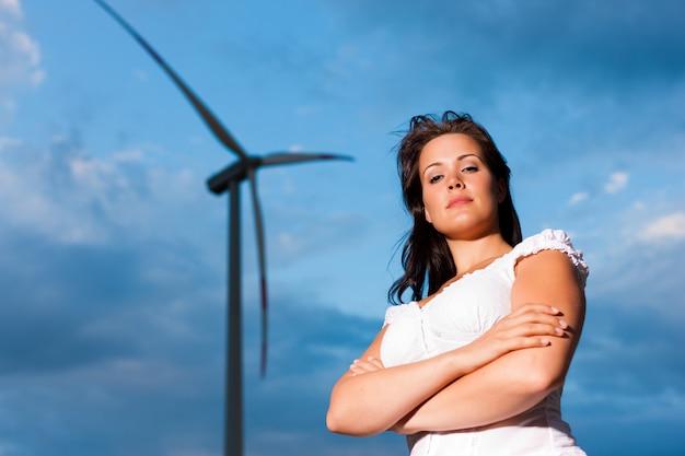 Die frau, die mit den armen aufwirft, faltete sich vor windmühle mit bewölktem himmel im hintergrund