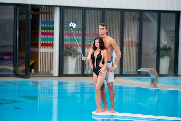 Die frau, die nahe swimmingpool aufwirft, macht selfie foto mit selfie stock
