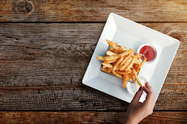 Die frau, die pommes-frites isst, dienen auf metall mesh flying sieve mit dip zwei