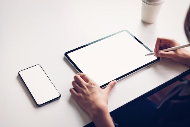 Die frau, die tablettenschirmfreien raum auf dem tisch verwendet, verspotten oben, um ihre produkte zu fördern. zukunftskonzept und trend-internet für einfachen zugang zu informationen.