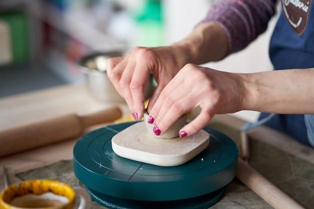 Die frau, die tonwaren, handnahaufnahme, unscharfer hintergrund macht, konzentrieren sich auf töpfer
