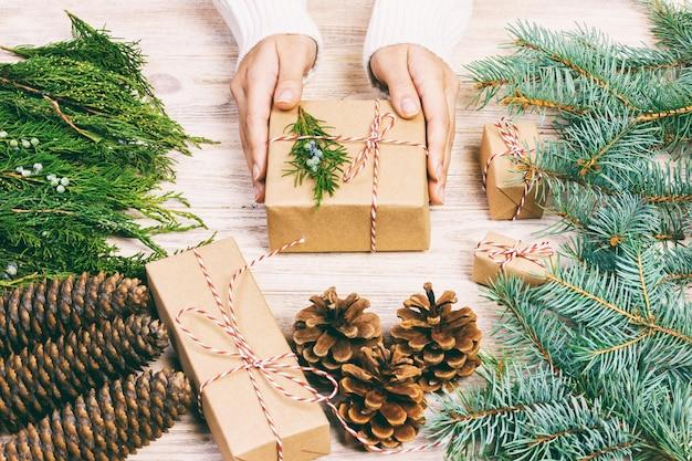 Die frau, die weihnachtsgeschenk einwickelt, mädchen bereitet weihnachtsgeschenke mit tannenbaum- und kiefernkegel vor. handgefertigtes geschenk