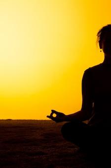 Die frau, die yoga im sonnenuntergangslicht praktiziert