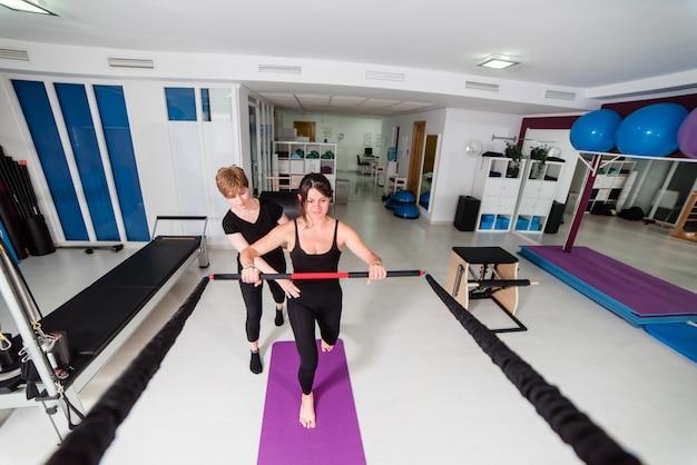 Die frau, die yoga pilates tut, trainiert in der turnhalle
