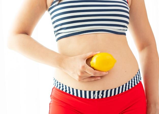 Die frau, die zitrone über ihrem unterleib hält, veranschaulichen ausgewähltes lebensmittel für gewichtsverlust