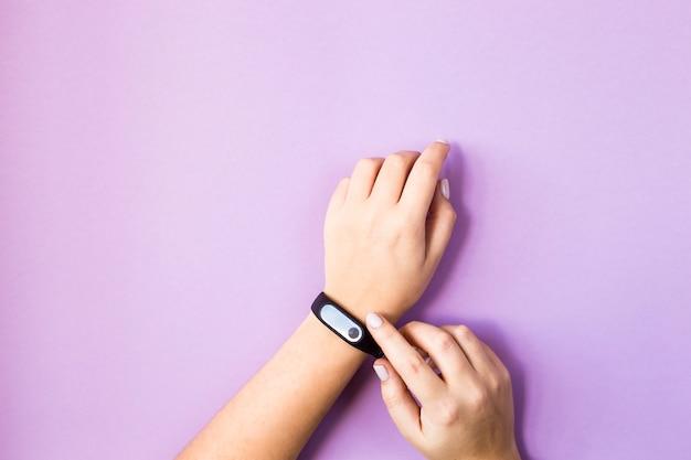 Die frau drückt den knopf ihres fitnessarmbandes an ihrem arm. auf hellem violettem hintergrund. gesunder lebensstil und fitness-konzept