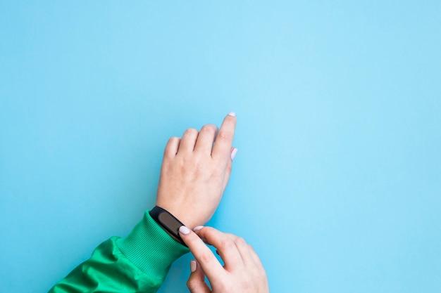 Die frau drückt ihr fitnessarmband auf ihren arm. hände in einer sportlichen hellgrünen jacke auf einem blauen hintergrund. gesunder lebensstil und fitness-konzept