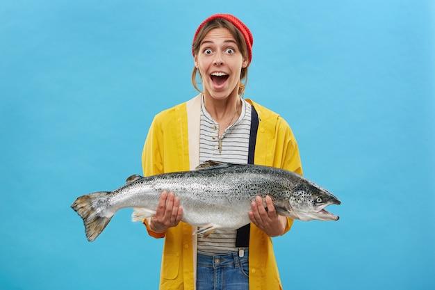 Die frau eines fischers, der einen riesigen fisch in der hand hält und einen überraschten gesichtsausdruck mit abgebeugten augen und heruntergeklapptem kiefer hat, glaubt nicht, dass ihre augen sich über den erfolgreichen fang freuen. glückliche schockierte fischerin mit forelle