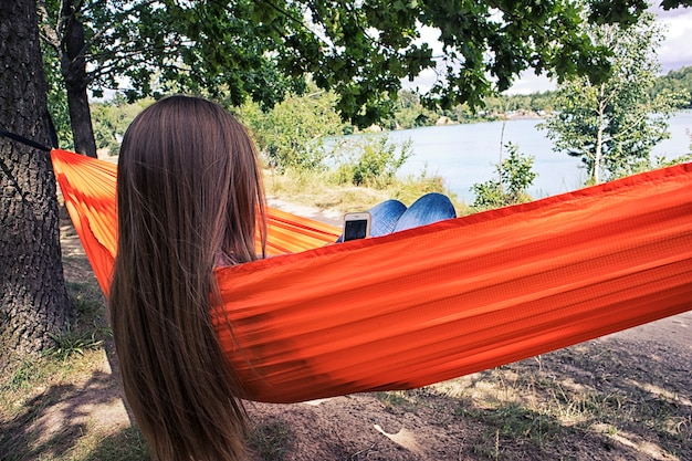 Die frau entspannt sich in der hängematte, während sie im telefon surft und auf den see schaut